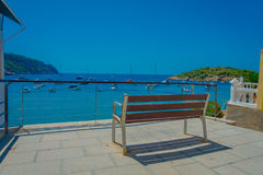 Beautiful sunny day in Sant Elm, with a public chair to enjoy the view in Majorca, with people enjoying the water, in Stock Photos