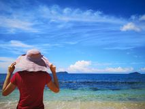A beautiful sunny day and a woman standing looking away further way ocean view. royalty free stock photography