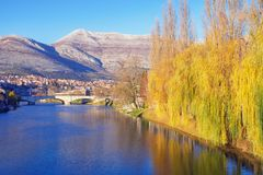 Beautiful sunny landscape, yellow trees of willows on river bank are reflected in water. Trebinje city, Bosnia and Herzegovina. Beautiful sunny landscape, yellow stock image