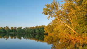 Beautiful sunny late summer day at dusk on the St. Croix River - reflection of trees on calm river waters.  stock photos