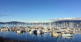 A beautiful sunny winter day overlooking a marina packed with sailboats along one of many beaches in Vancouver stock photography