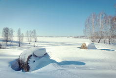 Beautiful sunny winter landscape. Rolls of hay on the snow Royalty Free Stock Photo
