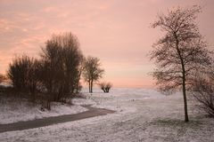 Beautiful Sunrise 2. A beautiful sunrise with trees, snow and dycke in the back royalty free stock images
