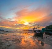 Beautiful sunrise above fishing boats on the beach. It creates a beautiful reflection in the water royalty free stock images