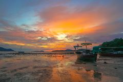 Beautiful sunrise above fishing boats on the beach. It creates a beautiful reflection in the water stock photo