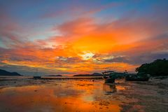 Beautiful sunrise above fishing boats on the beach. It creates a beautiful reflection in the water stock photos