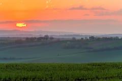 Beautiful sunrise above misty hill Stock Photos