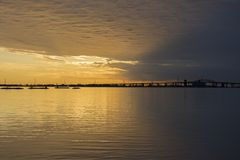 Free Beautiful Sunrise And Stormy Sky Over Tranquil Lake Waters, Bridge In Silhouette Stock Photography - 101181562