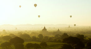 Beautiful sunrise at Bagan, Myanmar. The beautiful sunrise moment with the stunning view of hot air balloons fly over misty morning Bagan,  Myanmar Royalty Free Stock Photo