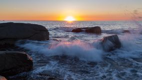 Sunrise over the ocean. Beautiful sunrise in a bay in Costa Brava with water splashing, Spain Stock Image