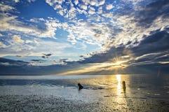 Beautiful sunrise on the beach, cloudy sky and the sun's rays Royalty Free Stock Photo