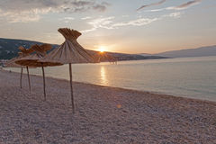 Beautiful sunrise on the beach. Sunrise on the beach of sea resort. Focus on umbrella reed Stock Images