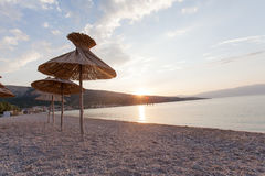 Beautiful sunrise on the beach. Sunrise on the beach of sea resort. Focus on umbrella reed Stock Photo
