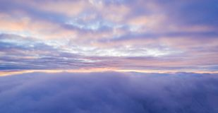 Beautiful sunrise cloudy sky from aerial view. Airplane view above clouds royalty free stock image