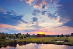 Beautiful sunrise and dramatic clouds on the sky. Flood waters of Narew river in Poland royalty free stock photography