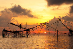 Beautiful sunrise. With fishing net and fisherman on the lake Stock Photo