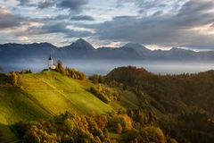 Beautiful sunrise landscape of church Jamnik in Slovenia with blue cloudy sky stock photo
