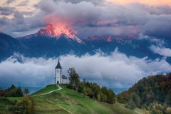 Beautiful sunrise landscape of church Jamnik in Slovenia with cloudy sky stock photography