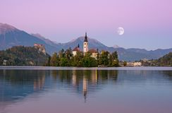Beautiful sunrise landscape of famous lake Bled in Slovenia with small church on green island on purple sky with moon and royalty free stock images