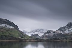 Beautiful Winter landscape image of Llyn Nantlle in Snowdonia Na. Beautiful sunrise landscape image in Winter of Llyn Nantlle in Snowdonia National Park with Royalty Free Stock Photography