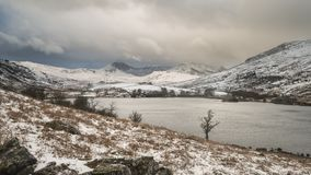 Beautiful Winter landscape image of Llynnau Mymbyr in Snowdonia. Beautiful sunrise landscape image in Winter of Llynnau Mymbyr in Snowdonia National Park with Stock Photo