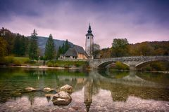 Beautiful sunrise landscape of lake Bohinj, Triglav National Park, Julian Alps in Slovenia with church and arch bridge on blue royalty free stock image