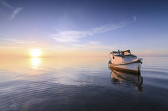 Beautiful sunrise with a little old boat abandoned in the sea Stock Image
