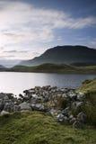 Beautiful sunrise mountain landscape reflected in calm lake Stock Images