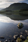Beautiful sunrise mountain landscape reflected in calm lake. Countryside landscape and mountains in beautiful morning light reflected in calm Cregennen Lakes in royalty free stock photography