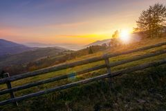 Beautiful sunrise in mountains. Countryside scenery in autumn. fence along the rural fields. distant mountains in haze royalty free stock photo