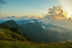 Beautiful sunrise in the mountains or hills above clouds Phu Chi Fa Stock Photography