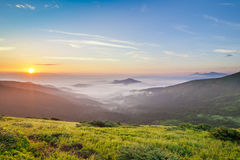 Beautiful sunrise in mountains with white fog below Stock Photos