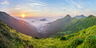 Beautiful sunrise in mountains with white fog below panorama Stock Images