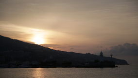 Beautiful sunrise over a beacon in Yalta stock footage