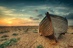 Beautiful Sunrise over Boats. A beautiful sunrise over a wooden fihing boat on s shingle beach Royalty Free Stock Images