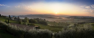 Beautiful sunrise with some fog between the hills with vineyards. Beautiful sunrise over Castellina in Chianti with some fog between the hills with vineyards in Stock Photography
