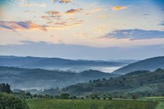 Beautiful sunrise with some fog between the hills with vineyards. Beautiful sunrise over Castellina in Chianti with some fog between the hills with vineyards in Royalty Free Stock Images