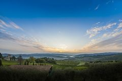 Beautiful sunrise with some fog between the hills with vineyards. Beautiful sunrise over Castellina in Chianti with some fog between the hills with vineyards in Stock Image