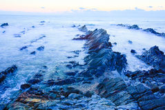 Beautiful sunrise over cretaceous sedimentary rock coastline Stock Photos