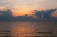 Beautiful sunrise over the horizon in the sea with clouds, Hua Hin, Thailand. Royalty Free Stock Photo