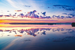 Beautiful sunrise over lake. Reflection of clouds of the sky in lake at sunrise Stock Photography