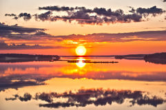 Beautiful sunrise over lake. Reflection of clouds of the sky in lake at sunrise Royalty Free Stock Image