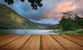 Beautiful sunrise over lake and mountains with wooden planks flo Royalty Free Stock Images