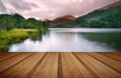 Beautiful sunrise over lake and mountains with wooden planks flo Stock Image