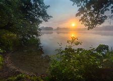 Beautiful sunrise over misty lake. Royalty Free Stock Image