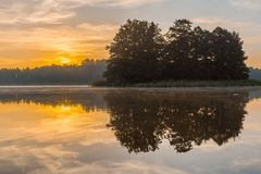 Beautiful sunrise over misty lake. Royalty Free Stock Images