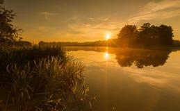 Beautiful sunrise over misty lake. Royalty Free Stock Photos