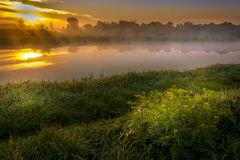 A beautiful sunrise over a misty meadow and a river Stock Image