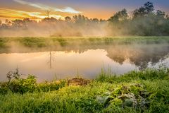 A beautiful sunrise over a misty meadow and a river. Beautiful sunrise over misty meadow and river, fog over the meadow, sun in the mist mystical morning in stock photo