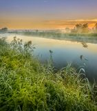A beautiful sunrise over a misty meadow and a river Royalty Free Stock Photography